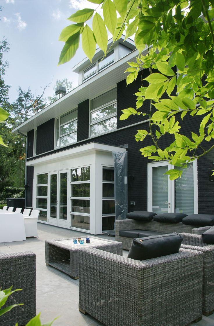 Achterzijde woning met erker met daarin openslaande tuindeuren.