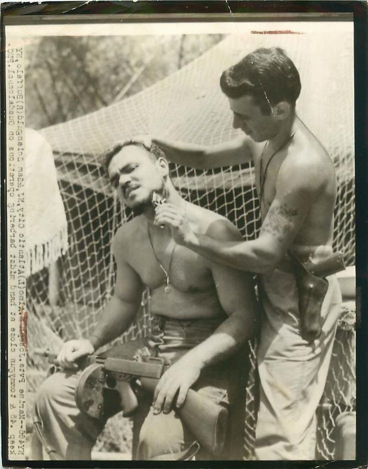 1942- U.S. 1st Division Marines on Guadalcanal keep their .45 and Tommy gun even while shaving.