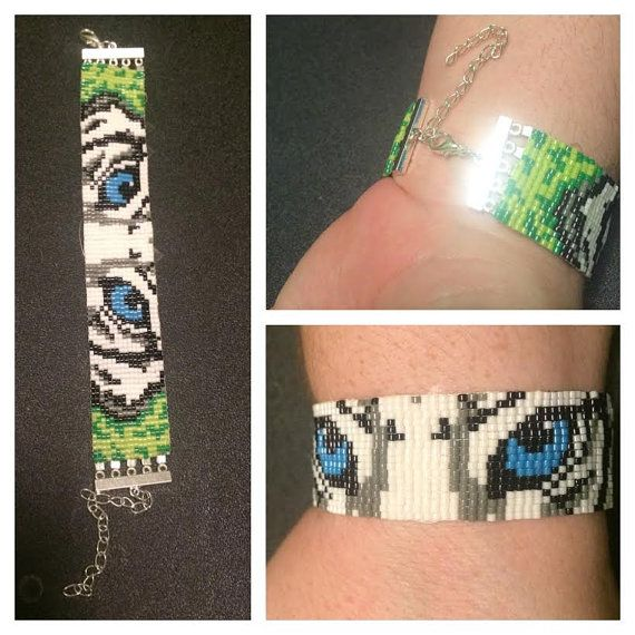 A beaded Loom bracelet with a White Siberian Tiger that has blue eyes, it has an adjustable metal clasp. fits any adult size wrist