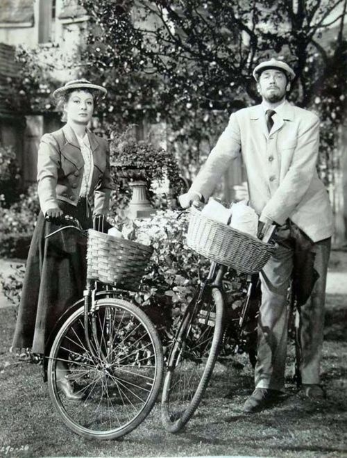 Greer Garson and Walter Pidgeon stand by their bikes. in Madam Curie!