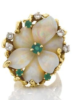 A carved opal, emerald, and diamond flower ring. Carved opal flower measuring approximately 26.1 x 19.5 x 7.7mm; signed Pac G.; mounted in eighteen karat gold.