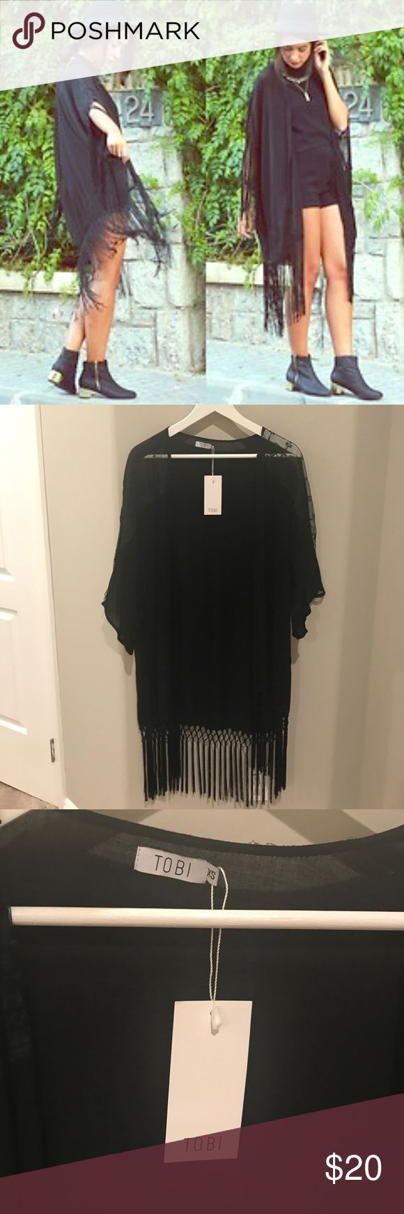 Black lace & fringe kimono Tobi brand. Size xs but can fit a small. Lace shoulders, fringe bottom. Top back right has 2 small holes, not noticeable. I received it from tobi like this but didnt realize till much later. Perfect for festival, as a cover up, or a night out. Very lightweight Tobi Jackets & Coats Capes