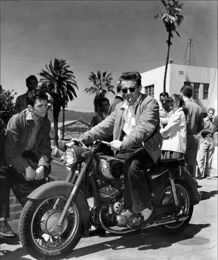 James Dean showing off his Triumph motorcycle on the Warner Lot, 1954.