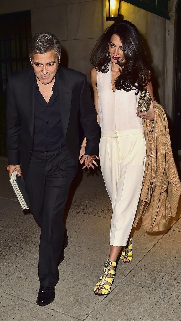 Amal Clooney ditched her dress for date night with George Clooney, choosing a white jumpsuit, yellow strappy heels, and golden accessories.