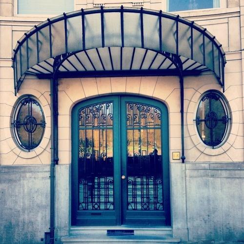 Mooie deur in gekruld ijzer en glas met ernaast ovalen vensters en erboven een metalen luifel (81/365). Gebouwd in 1925 naar een ontwerp van de architecten A. en O. Vande Voorde. Naar verluidt was dit appartementsgebouw de eerste hoge bouw in Gent. Ik ben deze deur al honderd keer voorbijgewandeld, maar het was pas toen ik een foto nam dat ik er een papegaai in zag.