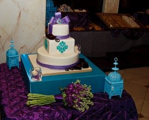 This three tier wedding cake was designed for a wedding which had a theme that was a mix of modern and classic. The clients requested a clean design that incorporated the bride's favorite color, purple, and the mother of the groom's favorite color, turquoise. A purple fondant band wraps around the base of the top and bottom tier. A turquoise damask pattern decorates the square shaped middle tier. A fondant bow with a turquoise and purple edible broach is the perfect union of the two styles.