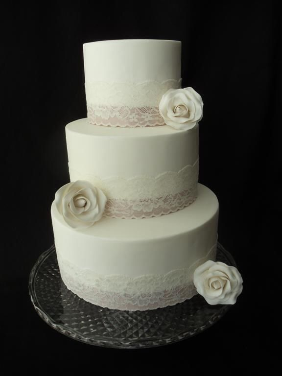 Lace ribbon wedding cake, bottom 2 tiers with purple ribbons under lace and purple flowers