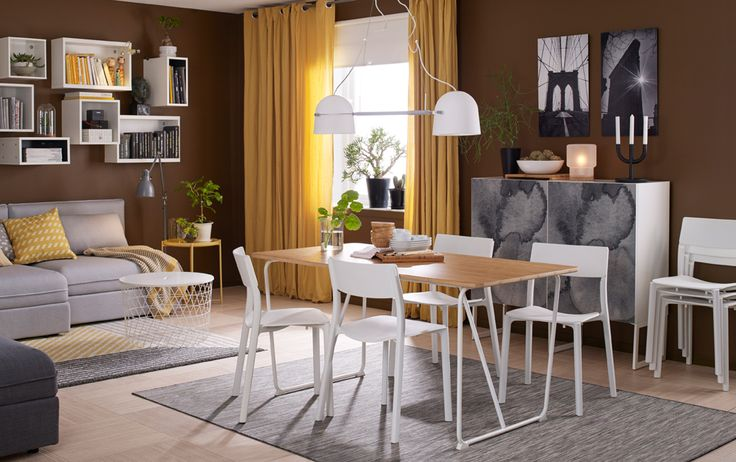 A medium-sized dining room furnished with a dining table in bamboo with white legs and with room for four people shown together with four white chairs.
