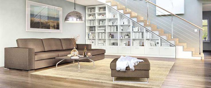 Das maßgefertigte, weiße Regal mit Schubladen passt millimetergenau in die Nische unter der Treppe und bietet viel Platz für Bücher und Deko. Harmonisch fügt sich das maßgefertigte Sofa mit Longchair aus der Kollektion Wiesbaden in das Raumambiente ein.
