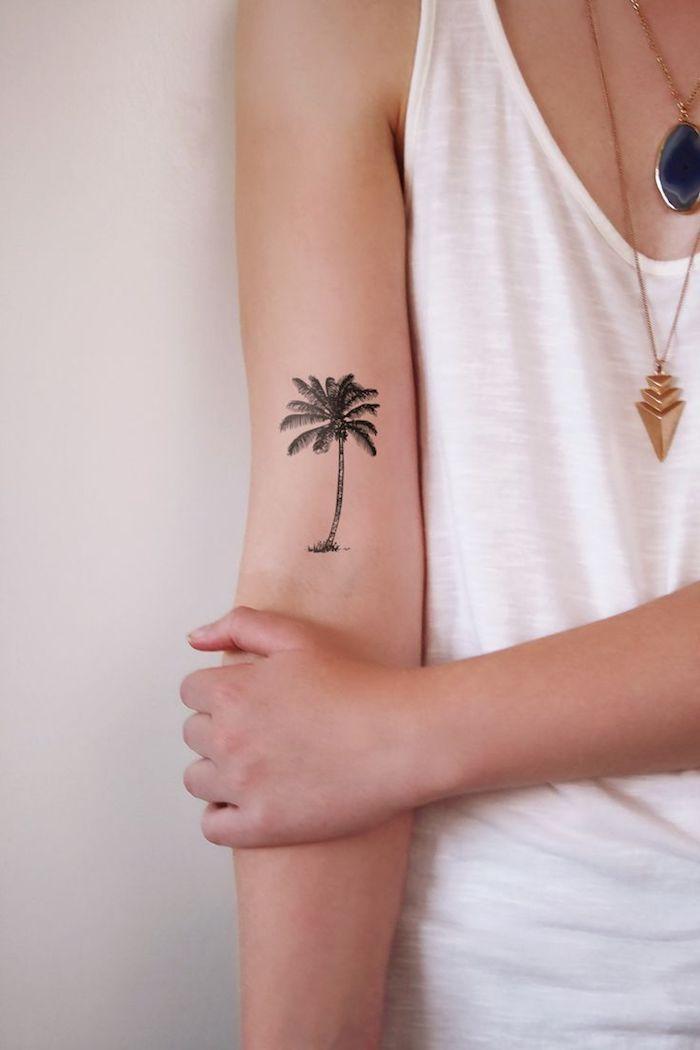débardeur blanc pour femme, collier pendentif en or avec pierre noire, dessin sur la peau à design palmier