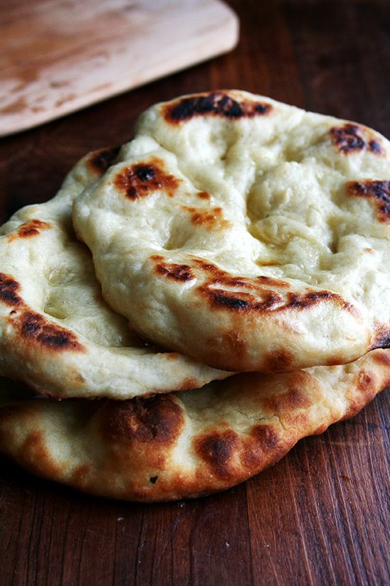 """Naan recipe - """"There are a dizzying number of recipes out there for naan, some calling for both baking powder and baking soda, many calling for yogurt and milk, some coated with oil before baking, others with water. I have tried a number of recipes these past few weeks, and this is my favorite. The dough is wet and sticky and requires no kneading."""""""