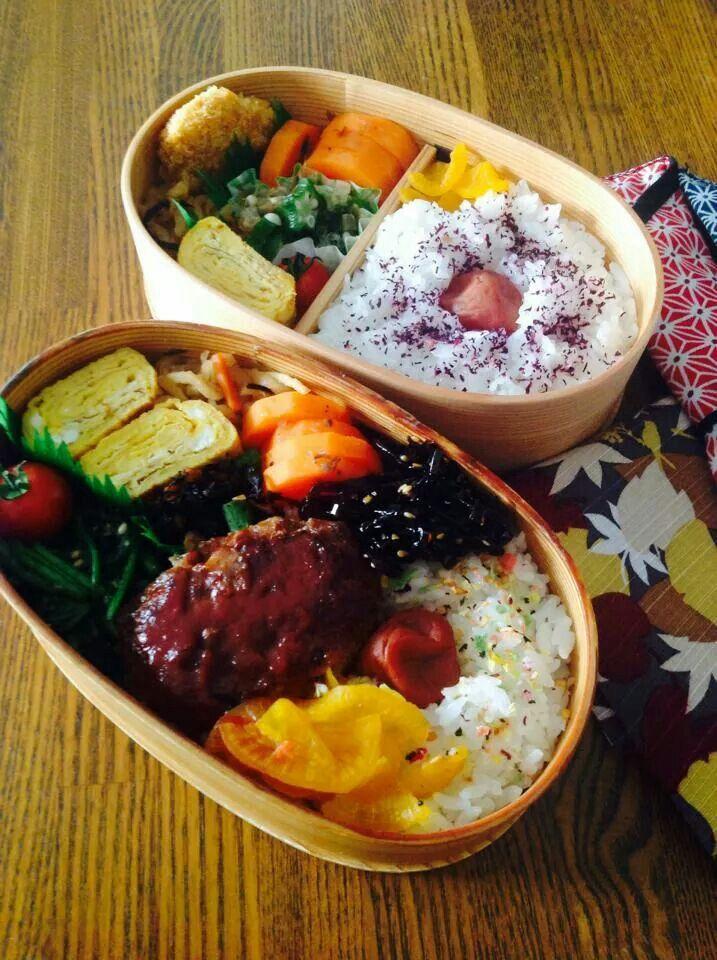お弁当部 /// The one in front appears to have a hamburger steak (Japanese style), pickled daikon, rice with umiboshi (pickled plum), wakame salad, steamed carrots, tamagoyaki, sauteed spinach (or blanched topped with soy sauce and sesame seeds), cherry tomato, and I'm not sure of the thing by the carrots and egg (looks like noodles). The back one appears to have pickled daikon, rice with umiboshi tamagoyaki, some sort of katsu dish, and a spinach dish