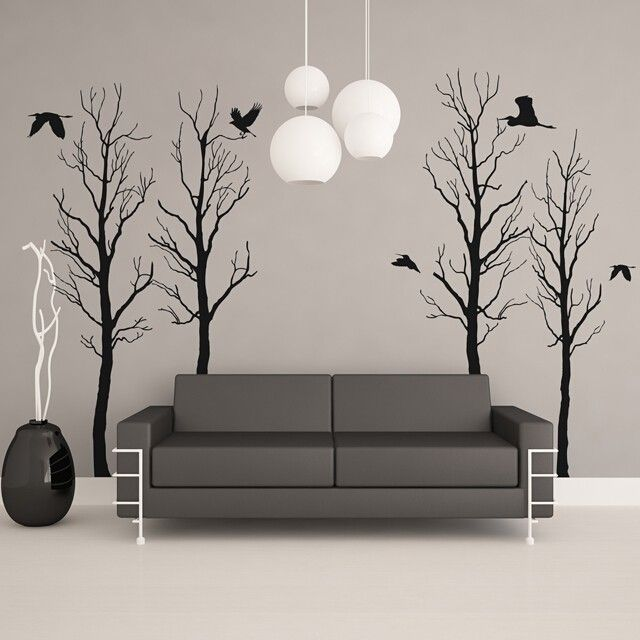 Black winter tree wall decals with 6 flying birds spaced apart in various locations all placed on a beige wall behind a modern gray couch and vase.