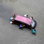 Residents push a car in flood waters in west Jakarta, Indonesia, January 18, 2013 | © Supri | REUTERS