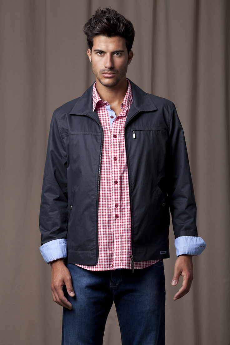 Dark blue jeans, red, checked shirt with blue button rim and cuffs, and navy blue zipped jacket with zipped pocket