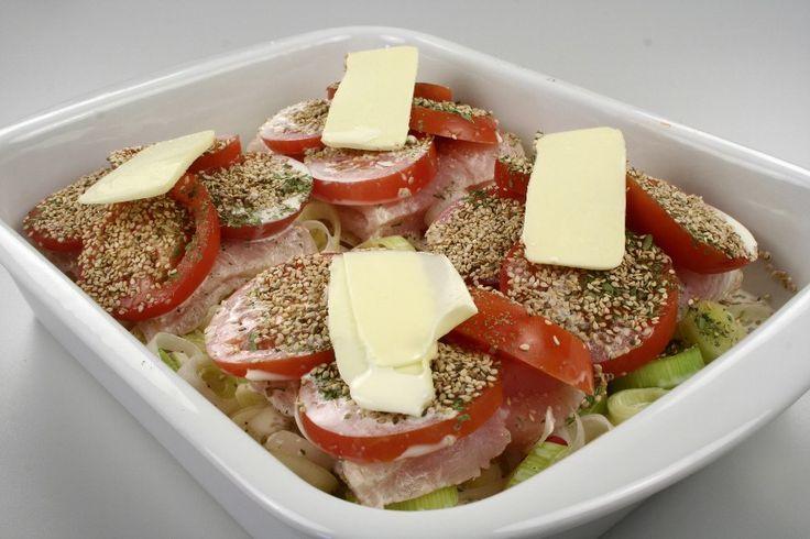 Et ovnfast gnides med smør.<br /> <BR> Porre og chili renses og snittes fint.<br /> Fisken tørres og tomaterne skæres i skiver.<br /> Fadet fyldes i lag. Krydder med salt, peber og estragon mel