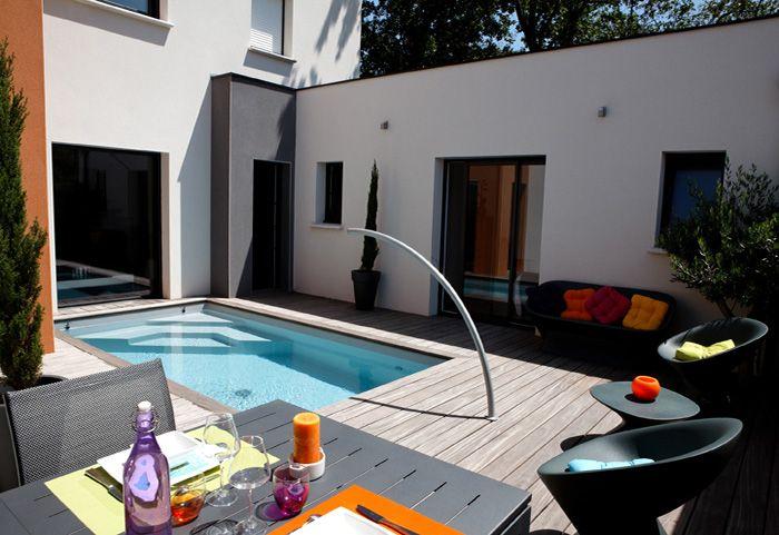 Nichée contre la maison, la piscine est visible des pièces à vivre et invite à profiter de l'extérieur. Dim 2,40 x 4,50 m, panneaux béton armé de 1,20 m et liner gris clair. Equipement : 1 projecteur à leds couleur, un arc de nage, couverture automatique immergée sous la terrasse. Terrasse bois. Réalisation Caron Piscines.
