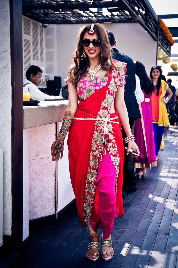 A stunning red and dark pink dhoti saree by Anamika Khanna for the mehendi ceremony of Payal Shah of WeddingSutra.