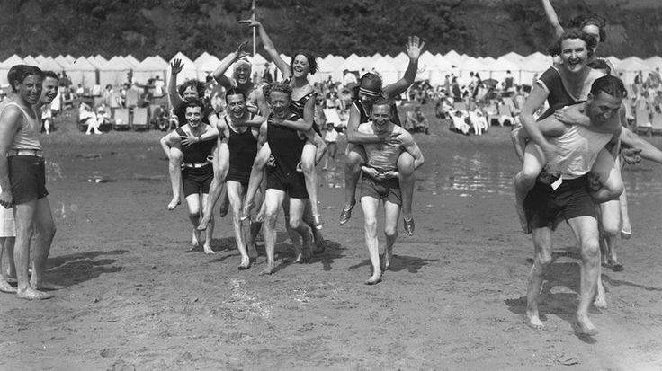 August 1928: Holiday makers have a piggy back race on the beach at Shanklin on the Isle Of Wight. (Topical Press Agency/Getty Images) | Fun in the Sun: Vintage Beach Photos | The Weather Channel