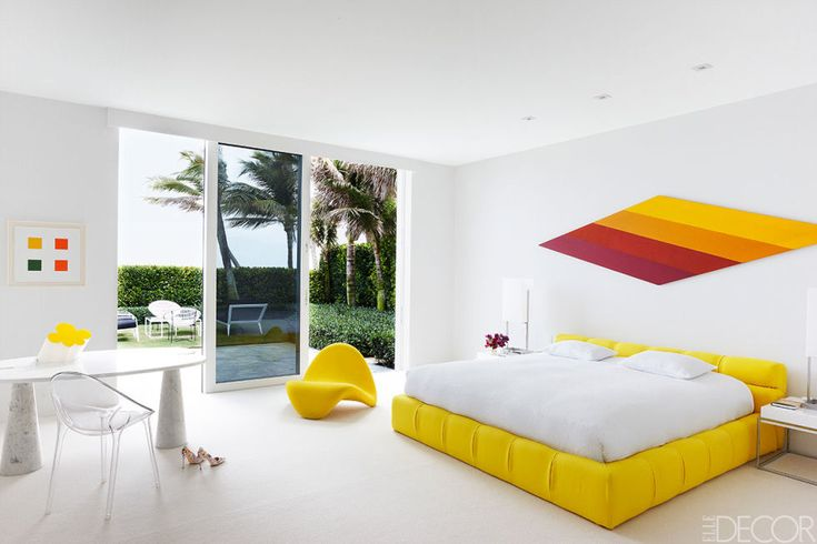 "In the master bedroom of Lisa Perry's Palm Beach home, Kenneth Noland's painting ""Florio"" hangs above a bed by Patricia Urquiola from B&B Italia. The yellow chair is vintage Pierre Paulin, the desk is by Angelo Mangiarotti, and the acrylic chair is by Philippe Starck for Kartell. Tour the rest of the home."