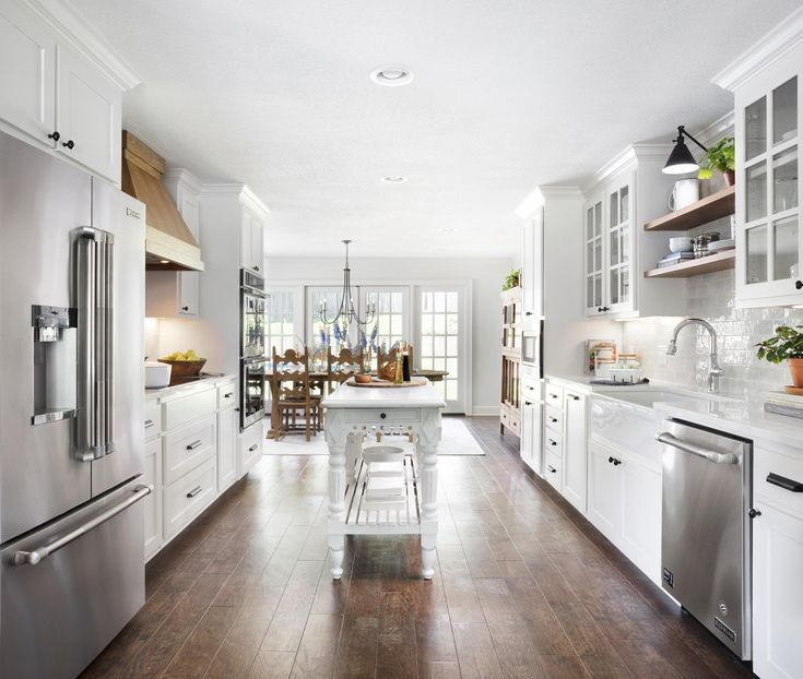 The original kitchen layout was slightly closed off from the rest of the home, which made it feel dark and smaller than it actually was. We opened it up to make a wide galley-style layout with an antique island in the middle for added prep space.