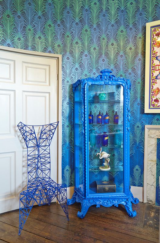 Blue and green peacock wallpaper from the Osborne and Little Eden collection cover the bathroom in the Matthew Williamson suite at Aynhoe Park. The interior of the bathroom features a symmetrical metal chair and a royal blue cabinet that stores blue lotion bottles.