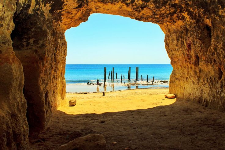 Port Willunga, Port Willunga, Australia - There's something pretty special about this place - it's probably the most underrated beach in Australia. This shot was taken from one of many caves carved into the cliff face by early fishermen to store their boats and nets. Get there early on a sunny day to set up in the shade. It's not a bad little spot to watch the waves lapping at the foot of those 150 year old jetty ruins either!    #localgem #southaustralia #australia #beach…