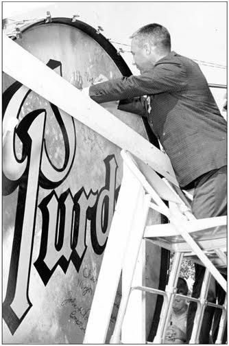 Gus Grissom signing Purdue University Big Bass Drum during 'Gus Grissom Day' in Mitchell, Indiana on June 16, 1962.