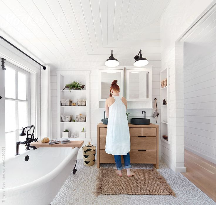 Woman washing hands in bathroom in rustic modern farmhouse by Trinette Reed for Stocksy United