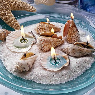 Seashell candles nestled in sand are a lovely touch on a beachy tabletop.