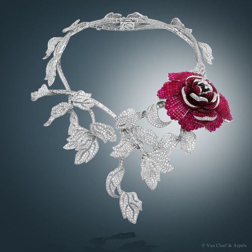 Pivoine Mystérieuse necklace, Palais de la chance™ collection White gold, diamonds, red gold, Mystery Set™ rubies The Pivoine Mystérieuse necklace from the Palais de la chance collection™ - revealed at the TEFAF Maastricht in March 2014 - adorns the neckline with a garland of leaves in delicate openwork, set with round and baguette-cut diamonds and features a spectacular pivoine detachable clip with Mystery Set™ rubies and diamonds. This masterpiece has required more than 6,000 hours of ...