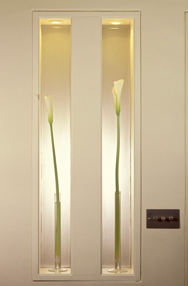 Narrow, rectangular display niches each with a concealed downlighter carry single stemmed lilies in slim clear glass vases, in the dining room of an apartment in London. UK ©Michael Freeman