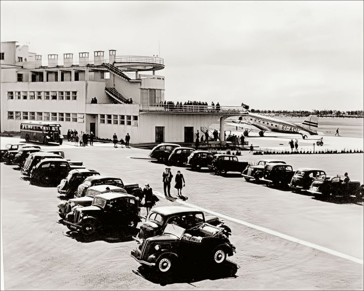 Car parking at Dublin Airport in the early 1950s in the days before strict airport security. Aer Lingus DC-3 'EI-ACI' is parked on the ramp. The building's open balconies were very popular, and were open to the public, as was the airport's large restaurant which gave a view of the airfield. For a time dinner-dances were held in the airport at night. The balconies were eventually closed for security reasons.