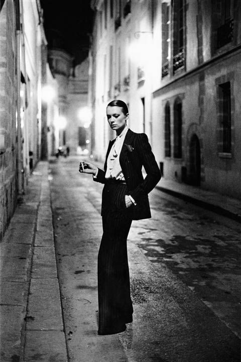 A dark Parisian alley. Hazy street lights. A nonchalant pose. Helmut Newton's gender-bending 1975 photograph is as famous as its subject — Yves Saint Laurent's Le Smoking, in pinstripes.