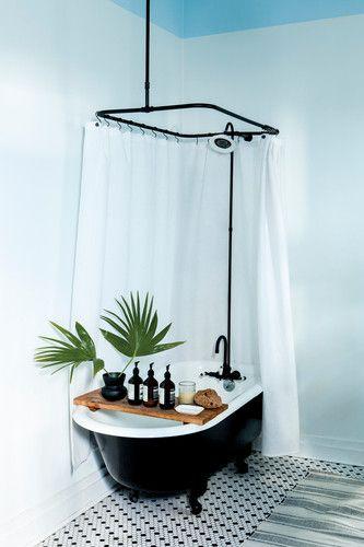 Dans la salle de bain la baignoire retro vintage sur pieds noire est accueillante et confortable grace à ce plateau, pont de bain qui permet d'accueillir quelques plantes ou bougie et un livre pour bouquiner depuis son bain moussant.