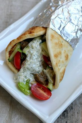 Slow Cooker Beef Gyros Recipe with Tzatziki sauce (cucumber and yogurt), grape tomatoes, crisp romaine lettuce, soft onions and wrapped in soft, pita bread.