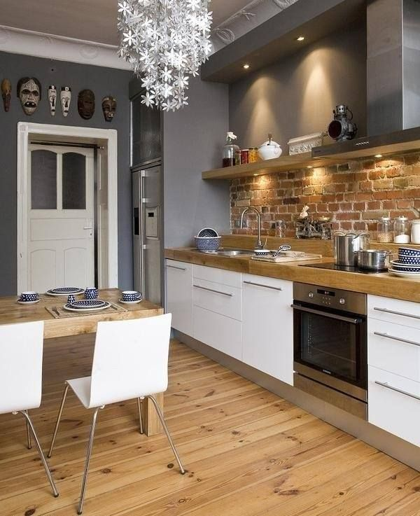 white grey kitchen with exposed brick and natural wood.: