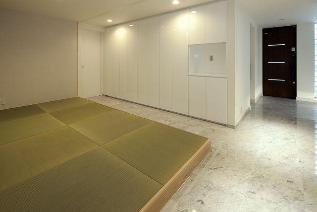 広い玄関ホールの大理石とピアノ塗装の収納キャビネット、その前に設えた畳スペースは、引戸のレールは見えませんが、大理石の床に掘り込んである手の込みよう!