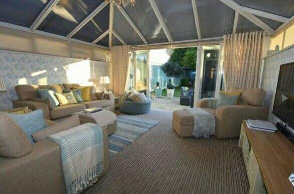 Beautiful conservatory with blue & nude furnishings