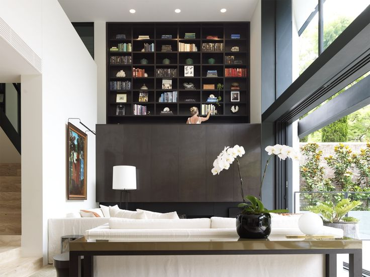 Tobias Partners - Cooper Park House. Bookcase with 42 niches soars over the open-plan living room. White slip-covered sofas. Scatter cushions in Jim Thompson The Thai Silk Company by Sarah Davison. 'Lisbon' floor lamp by Christian Liaigre. Artwork by Ray Crooke.
