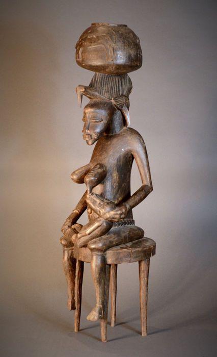 Hoogte 85 cm. Breedte 25 cm. Diepte 24 cm. Hout. Gekocht in een Britse veilinghuis. Zeer expressieve vrouwelijke figuur is van de Senufo bevolking van Ivoorkust (Cote d'Ivoire), Mali en Burkina Faso. Zittend op een ingerichte kruk, is ze heel goed gesneden met de kenmerken van de klassieke beeldhouwkunst van de Senufo in termen van details en stijl. De Senufo (de Franstalige spelling Senoufo wordt vaak gebruikt) zijn een etnische groep die bestond uit verschillende deelgroepen van Gu...