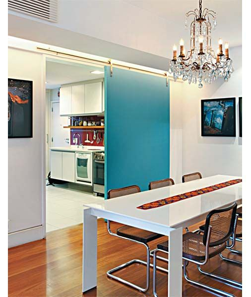 """4. Entre a cozinha e a sala de jantar, a porta de correr, um painel único e liso de MDF com 5 cm de espessura, se faz presente como um quadro pintado de azul (Tintas Coral, ref. 36/333) no ambiente. """"A intenção era deixá-la marcante, com ferragens aparentes"""", diz a arquiteta Renata Bartolomeu. No teto, um rasgo em forma de L acompanha a viga invertida e embute iluminação indireta."""