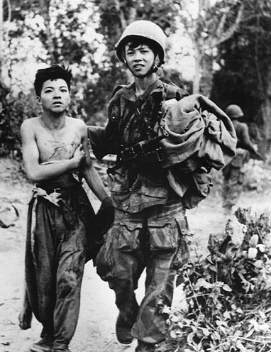 A Vietnamese paratroopers is taking away a wounded Viet Minh prisoner from combat zone. ~ Vietnam War