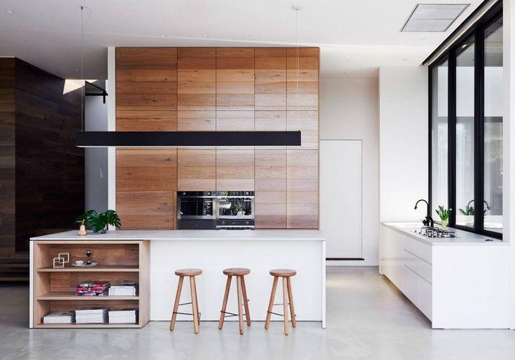 Cucina moderna minimal definita con falegnameria in rovere, banco realizzato in pietra colore bianco e accenti neri