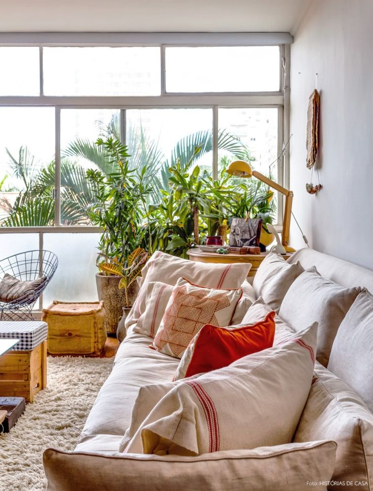 Sala de estar neutra com sofá bege, almofadas listradas e étnicas em tons terrosos.
