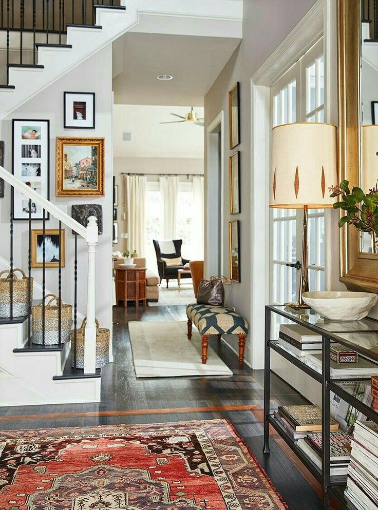 Visually interesting foyer with patterned rug, gallery wall staircase and mirrored console table.