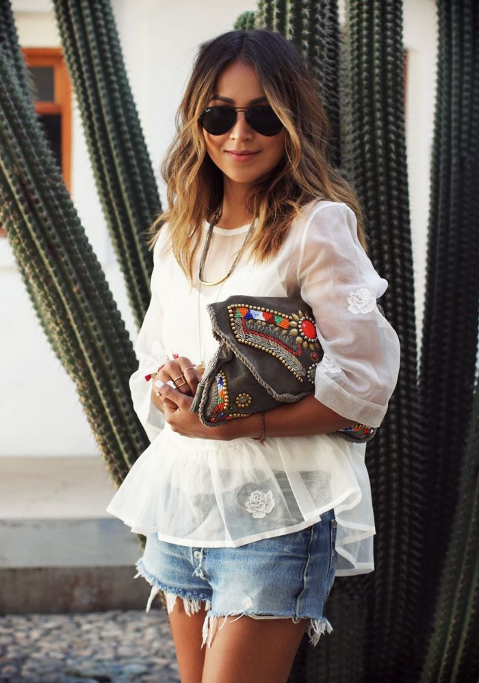 Blogger Sincerely Jules wears an Aritzia blouse, Levi's 501 vintage shorts with an Antik Batik embellished clutch for a complete bohemian chic look.