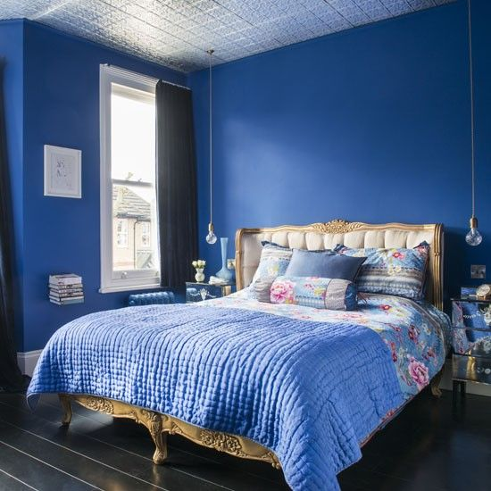 Bold sapphire blue walls, black floorboards and a stunning gold French-style bed create a luxe, boudoir look in the master bedroom. Mirrored bedside cabinets with hanging crystal lights above intensify the romantic look of the room