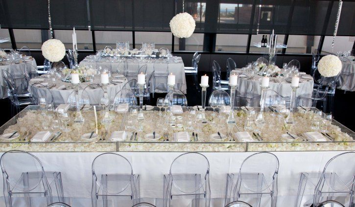an alternative to full acrylic wedding tables and a less expensive option is to use acrylic table boxes as featured below to create the illusion of a clear wedding table. These are also great because you can place rose petals, wedding flowers, and the like inside of the acrylic boxes as table decorations~
