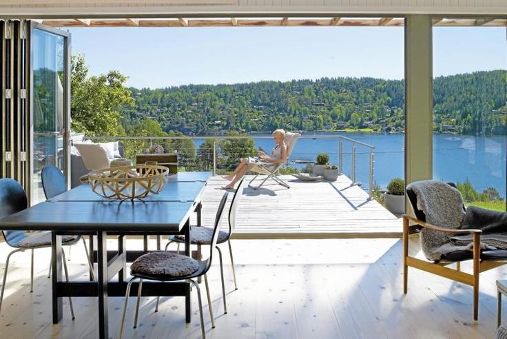INNE OG UTE: Fra kjøkkenet og stuen er det foldedører fra Schüco ut til terrassen. Det gir en følelse av å sitte ute selv om man sitter inne. Lampene, det henger to like fra stuetaket, er laget etter oppskrift fra rom123.